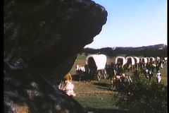 Montage of  covered wagons and settlers traveling cross country stock video footage