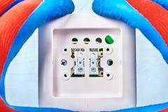 Montagem do interruptor da luz pelo trabalhador foto de stock royalty free