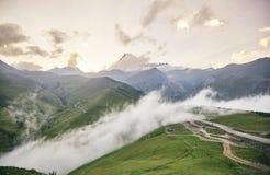 Montagem Kazbegi no sol de ajuste Montanhas caucasianos de Geórgia foto de stock