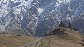Montagem próxima antiga Kazbek da igreja de trindade de Gergeti, montanhas de Cáucaso filme