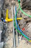 Montaggio dei cavi e dei tubi sotterranei in un programma di costruzione di alloggi Fotografia Stock
