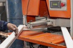 Montaggio della macchina delle strutture della finestra di plastica alla fabbrica fotografia stock