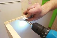 montaggio di mobilia con un trapano Fotografia Stock