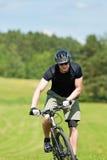 Montagna allegra dell'uomo che biking i prati pieni di sole in salita Fotografia Stock