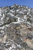 Montagna alta Cliff Rock Face con la neve di inverno e ghiaccioli su cielo blu Sunny Day Immagini Stock Libere da Diritti