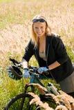 Montagna che biking i prati pieni di sole allegri della giovane donna Immagini Stock