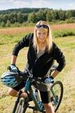 Montagna che biking i prati pieni di sole allegri della giovane donna Immagini Stock Libere da Diritti