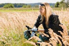 Montagna che biking i prati pieni di sole allegri della giovane donna Fotografia Stock