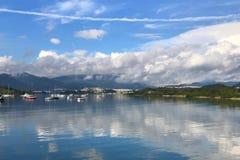 Montagna, cielo blu, barche, yacht e barche a vela sul lago Fotografie Stock Libere da Diritti