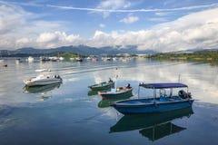 Montagna, cielo blu, barche, yacht e barche a vela sul lago Fotografie Stock