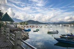 Montagna, cielo blu, barche, yacht e barche a vela sul lago Immagine Stock