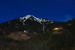 Montagna con la capanna della montagna e della neve di notte Fotografie Stock Libere da Diritti