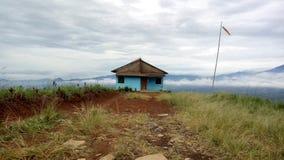 montagna con la casa diritta fotografie stock