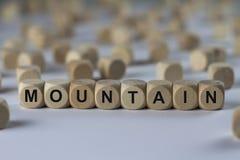 Montagna - cubo con le lettere, segno con i cubi di legno Fotografia Stock
