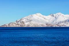 Montagna della neve con il fiordo in priorità alta (Norvegia vicino a Tromso) Immagine Stock