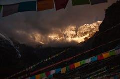 Montagna della neve con la bandiera di preghiera nella gloria di alba in Yubeng Immagine Stock