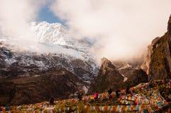 Montagna della neve con la bandiera di preghiera nella gloria di alba in Yubeng Fotografia Stock