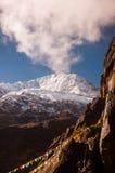 Montagna della neve con la bandiera di preghiera in Yubeng Fotografia Stock