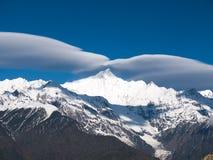 Montagna della neve di Meili protetta in nuvole Fotografia Stock