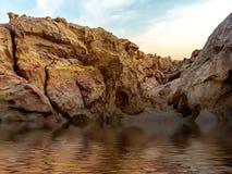 Montagna della roccia che circonda con acqua fotografia stock