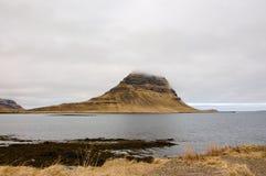 Montagna di Kirkjufell, raincloud, erba asciutta, Islanda Fotografia Stock