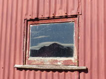 Montagna di punta della fronte riflessa nella finestra del granaio Fotografia Stock Libera da Diritti
