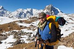 Montagna diritta della neve di resto del ritratto dell'uomo dell'alpinista di viaggiatore con zaino e sacco a pelo Immagine Stock Libera da Diritti