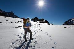 Montagna diritta della neve di resto dell'uomo dell'alpinista di viaggiatore con zaino e sacco a pelo Fotografia Stock