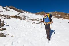 Montagna diritta della neve di resto dell'uomo dell'alpinista di viaggiatore con zaino e sacco a pelo Fotografia Stock Libera da Diritti