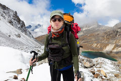 Montagna diritta della neve di viaggiatore con zaino e sacco a pelo della giovane donna sopra il lago Portra Fotografia Stock
