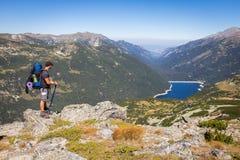 Montagna diritta di viaggiatore con zaino e sacco a pelo sopra il lago Fotografie Stock Libere da Diritti