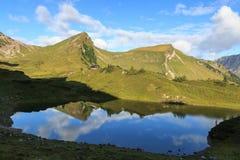 Montagna e capanna alpina con la riflessione in lago Fotografia Stock