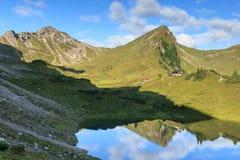 Montagna e capanna alpina con la riflessione in lago Immagine Stock