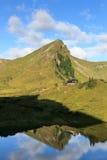 Montagna e capanna alpina con la riflessione in lago Immagini Stock Libere da Diritti
