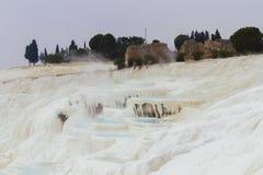 Montagna e terrazzi bianchi del calcare del travertino con le rovine della H fotografia stock libera da diritti