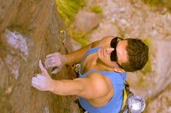 Montagna rampicante dell'uomo con gli occhiali da sole Immagine Stock