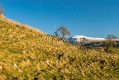 Montagna ricoperta neve con la luna fotografia stock libera da diritti