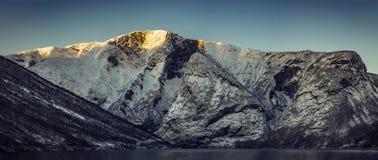Montagna ripida in Norvegia con neve sulla cima fotografia stock
