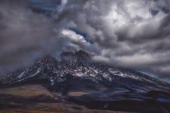 Montagna ripida in nuvole scure fotografia stock