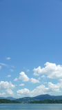 Montagna verde verticale, lago, cielo blu, nuvola bianca Immagine Stock