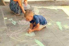 Montagnana, Włochy Sierpień 27, 2018: dzieci rysują z kredą na asfalcie na miasto ulicie zdjęcie stock