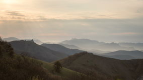 Montagne all'alba illuminata dai raggi del sole attraverso le nuvole video d archivio