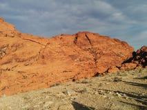 Montagne arancio rosse sbalorditive del deserto contro il cielo grigio nuvoloso immagini stock
