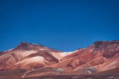 Montagne aride asciutte con suolo rosso nel deserto fotografia stock