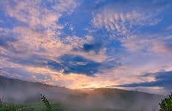 Montagne arrière de lever de soleil avec le brouillard à la colline d'herbe verte Images libres de droits