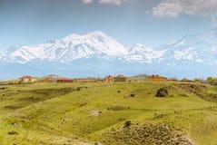 Montagne avec la neige et maisons dans l'avant Photo stock