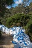 Montagne blu, Australia - 24 aprile 2019: Borse dei rifornimenti e dei materiali di manutenzione della pista che aspettano uso ac immagine stock