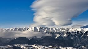 Montagne carpathienne roumaine dans l'horaire d'hiver avec les nuages et le ciel clair photos stock
