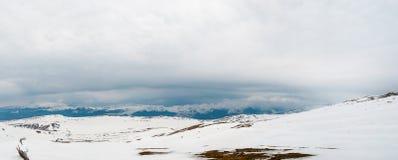 Montagne carpatiche coperte in neve e nuvole pesanti panoramiche immagini stock libere da diritti