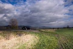 Montagne centrali ceche, repubblica Ceca - 11 novembre 2017: paesaggio autunnale soleggiato con la strada e l'automobile nera Ope Immagine Stock